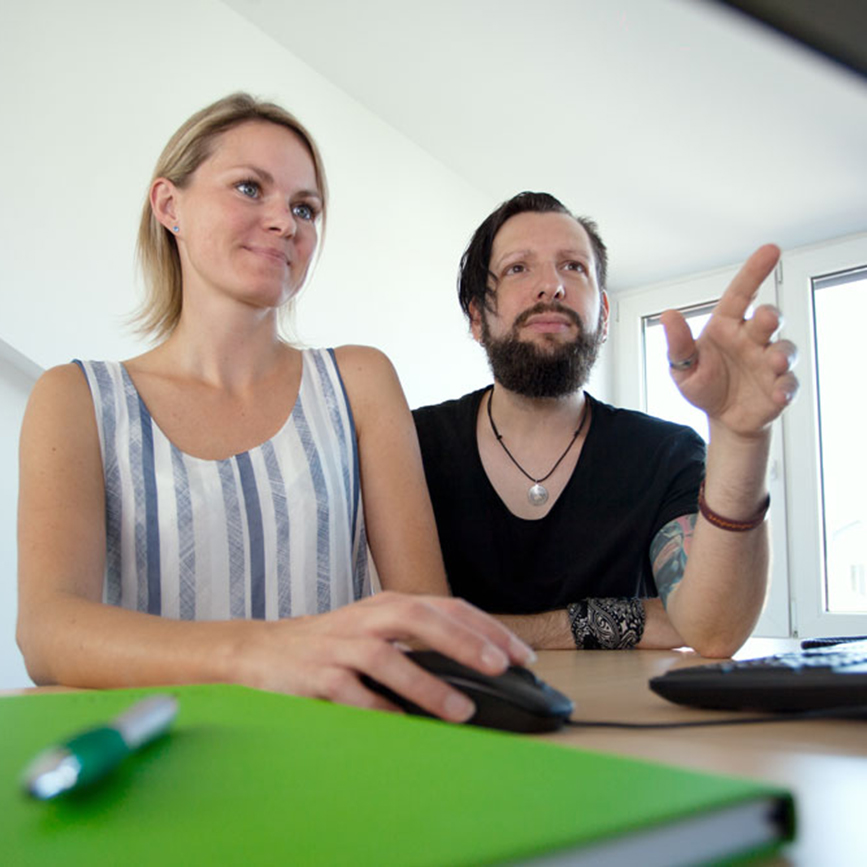 Zwei Mitarbeiter sitzen am Schreibtisch
