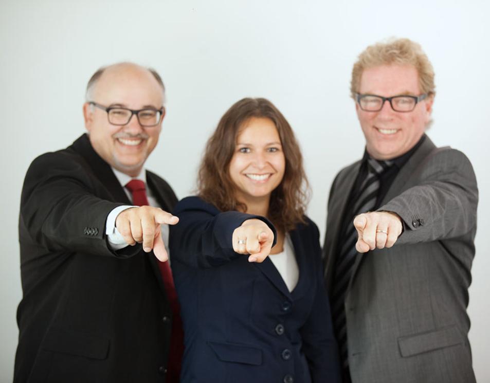 Drei Geschäftsführer zeigen mit dem Zeigefinger noch vorne