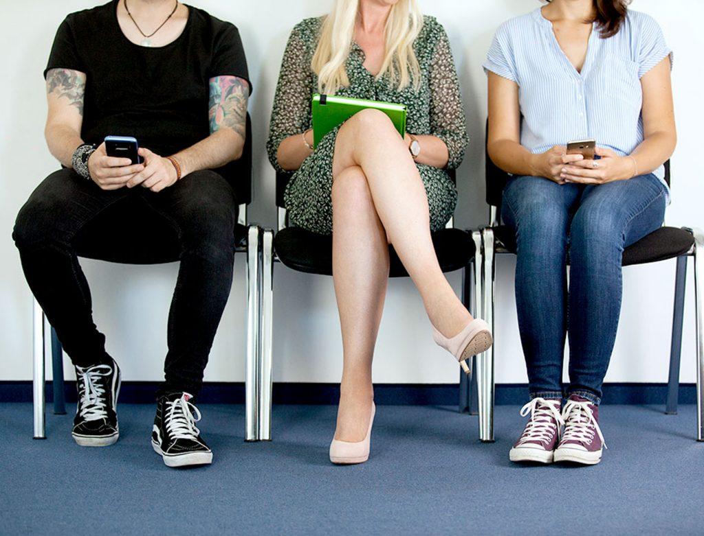 Drei Personen sitzen auf Stühlen und warten