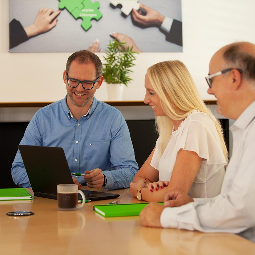 Besprechung von drei Personen vor einem Laptop